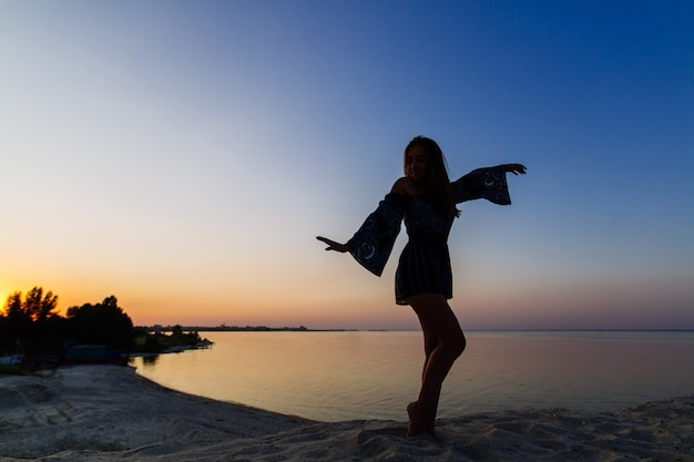 Silhouette slim woman posing on sandy beach. young loneliness woman enjoys sunset on a sandy beach. beautiful girl walking in the sunset outdoor Premium Photo