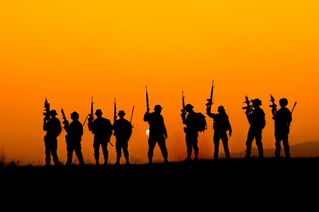 Silhouette of soldier team in sunset sky. soldier with machine gun patrolling Premium Photo