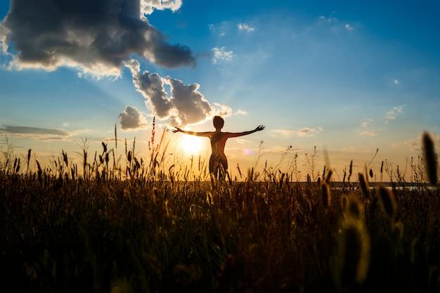 Siluetta di yoga di pratica della ragazza allegra nel campo ad alba. Foto Gratuite