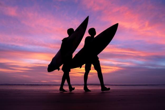 Silhouette surf athlete during sunset time at phuket thailand Premium Photo