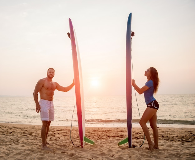 Silhouette of surfers couple holding long surf boards at sunset on tropical beach Premium Photo
