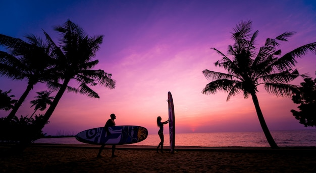 Silhouette of surfers couple holding long surf boards at sunset Premium Photo