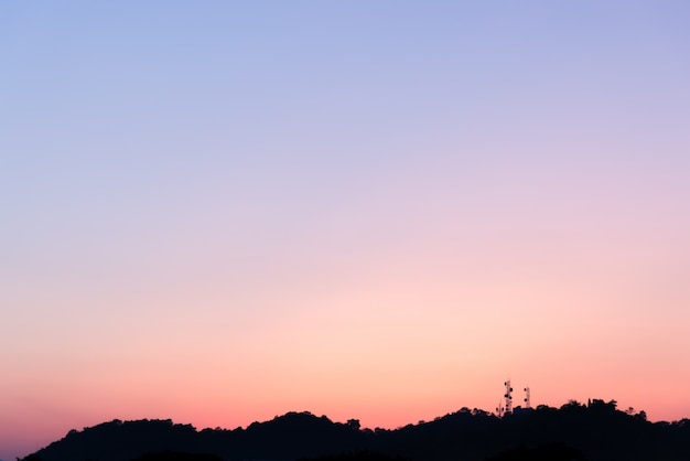 Silhouette of the telecommunications tower on the mountain with colorful sky. Premium Photo