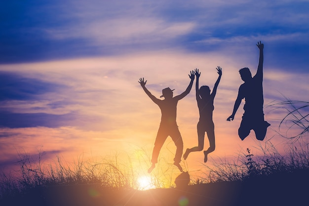 The silhouette of three people jumping Premium Photo