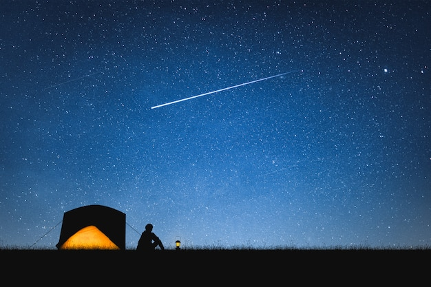 Silhouette of traveler camping on the mountain and night sky with stars. space background. Premium Photo