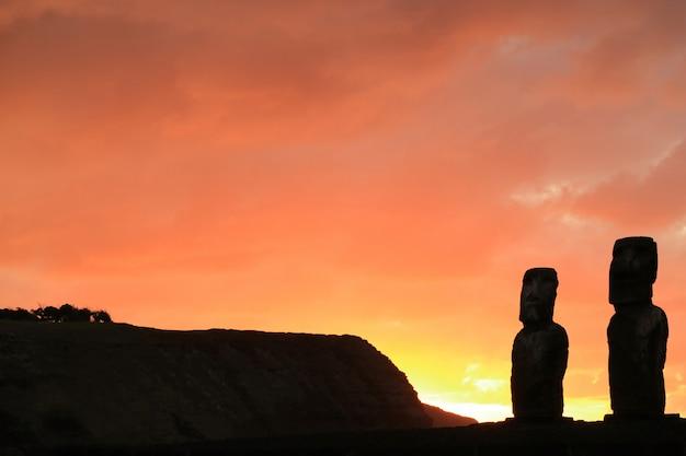 Silhouette of two of 15 moai statues at ahu tongariki against orange sunrise sky, easter island, chile Premium Photo