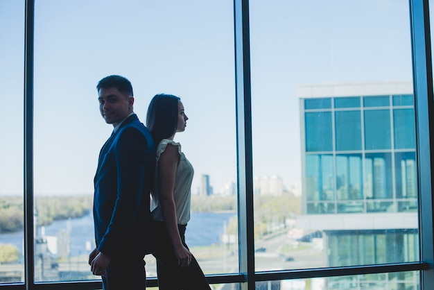 Silhouette of two business people leaning against each other Free Photo