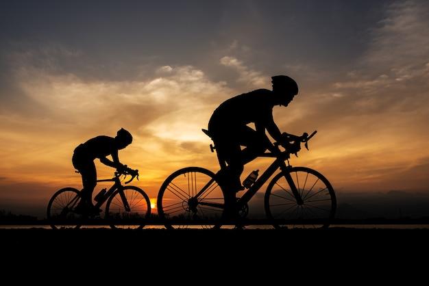 Силуэт два дорожных велосипеда велосипедист человек, езда на велосипеде утром. Premium Фотографии