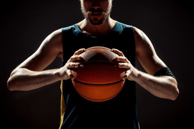 Profili il punto di vista di una palla del canestro della tenuta del giocatore di pallacanestro su spazio nero Foto Gratuite