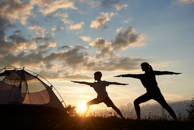 Silhouette view of yoga warrior pose exercising with couple near tent at the daybreak Premium Photo