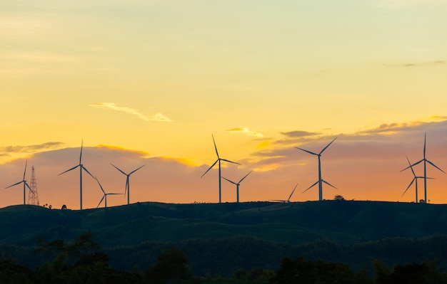 Silhouette of wind turbines at sunset in evening time, alternative energy Premium Photo