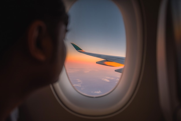 Silhouette wing of an airplane at sunrise view through the window. Premium Photo