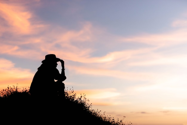 Silhouette of woman are using ideas on top of a hill in the sunset Premium Photo