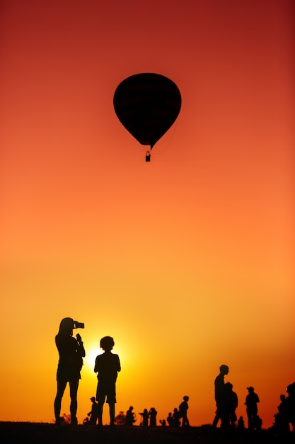 Silhouette of a woman holding a smartphone taking balloon