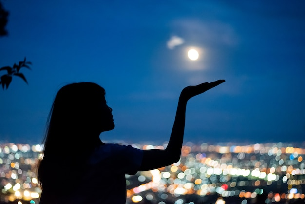 Silhouette woman portrait with full moon in city night light bokeh background , chiang mai ,thailand Premium Photo