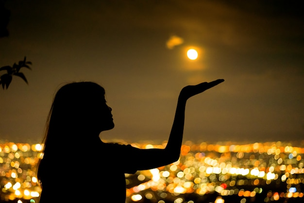 Silhouette woman portrait with full moon in city night light bokeh background Premium Photo