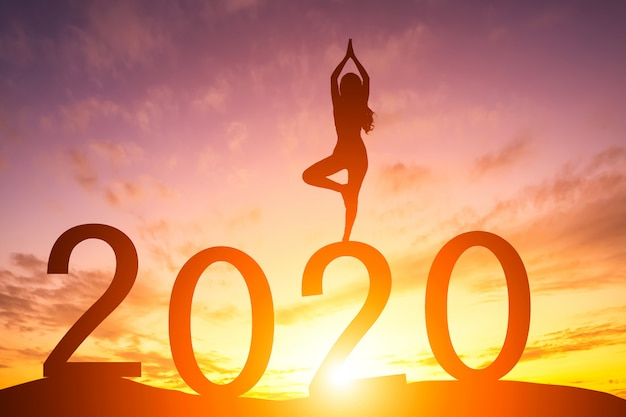 Silhouette of woman practicing yoga at sunrise with 2020 Premium Photo