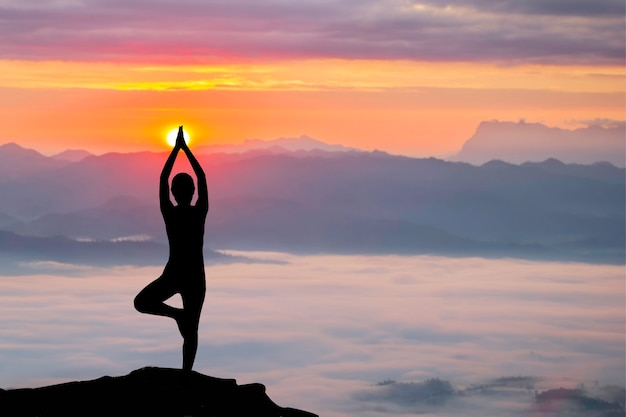Silhouette of woman practicing yoga at sunrise Premium Photo