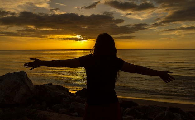 Silhouette of woman praying over beautiful sunset background Premium Photo