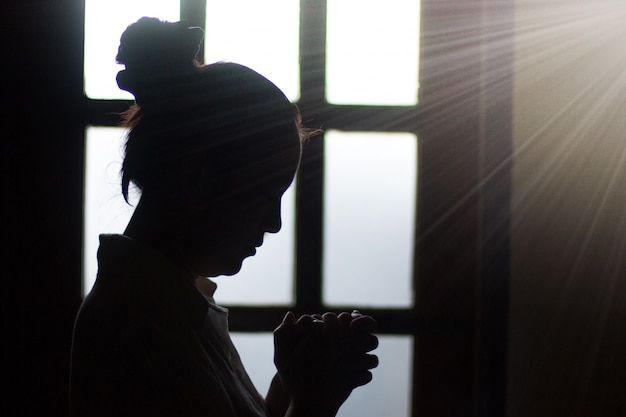 Silhouette woman prays at sunset near the window. Premium Photo