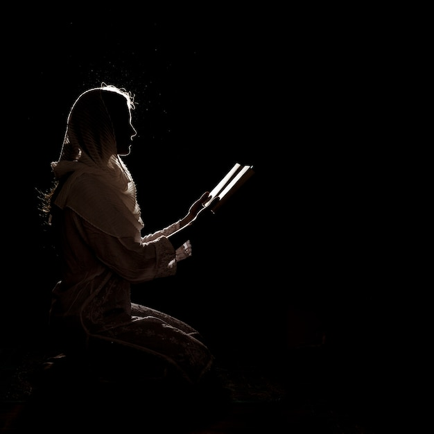 Silhouette of woman reading in quran Photo | Free Download