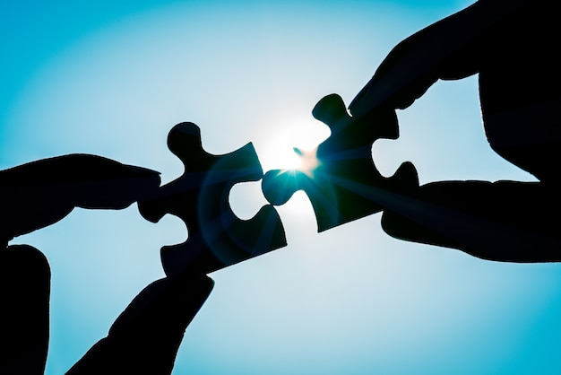 Silhouette woman's hand connecting a piece of jigsaw puzzle over sunlight effect. Premium Photo
