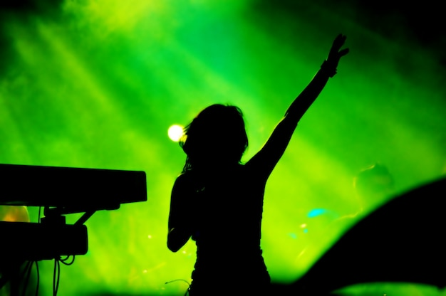 Silhouette of woman singing on green background Free Photo