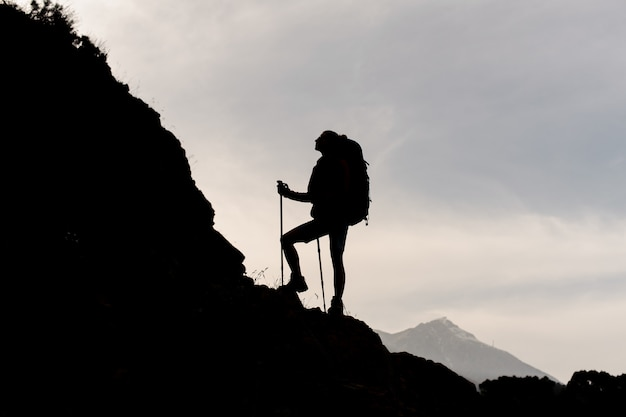 Silhouette woman standing on the rocks with hiking backpack and walking sticks Premium Photo