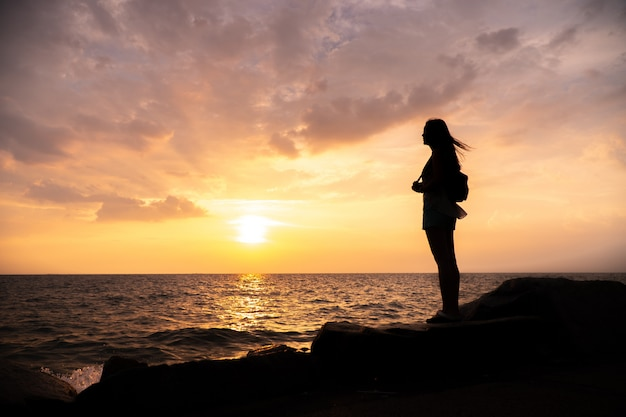 Premium Photo | Silhouette woman standing, sunset sky over horizon.