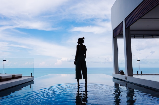 Silhouette of a woman walking on the water surface of the infinity pool of an expensive rich luxury villa on a mountain with a sea view Free Photo