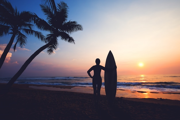 Silhouette Women Surfer On Tropical Beach At Sunset Landscape Of Summer And Palm Tree