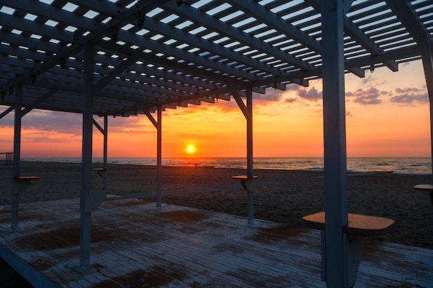 Silhouette of a wooden gazebo at sunset on a deserted beach Premium Photo