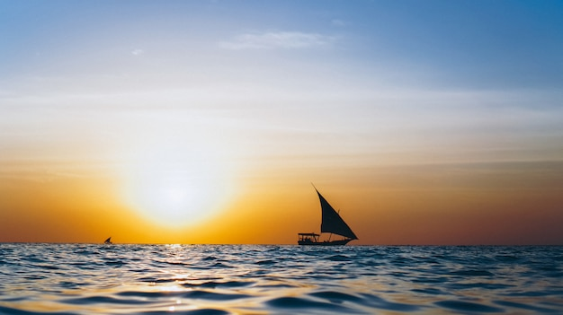 Silhouette of yacht in the open ocean on the sunset Free Photo