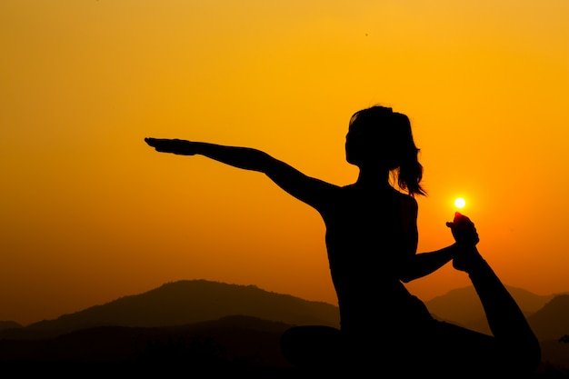 Silhouette - yoga girl is practicing on the rooftop while sunset. Free Photo