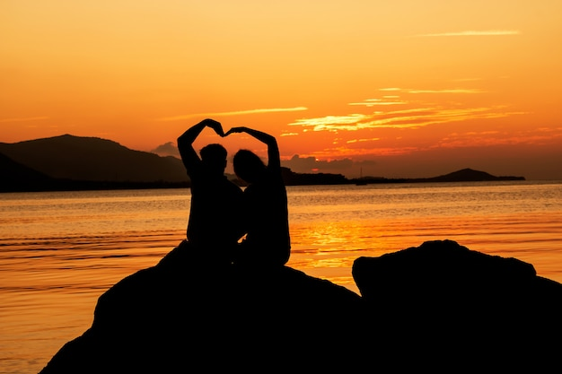 Silhouette of young couple in love at beach,sunset background Premium Photo