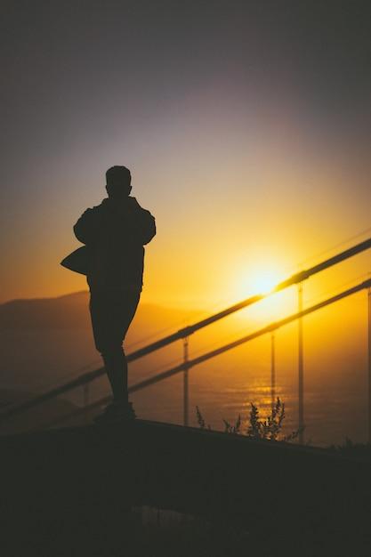 Siluetta di giovane maschio che cammina sulla scala dietro le rotaie della scala con la bella vista di tramonto Foto Gratuite