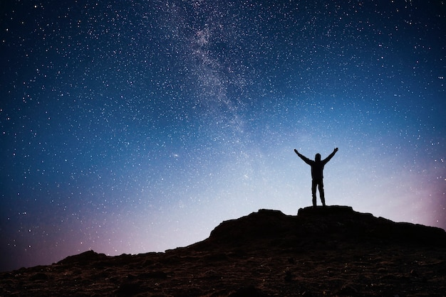 Silhouette young man background of the milky way galaxy on a bright star dark sky tone Free Photo