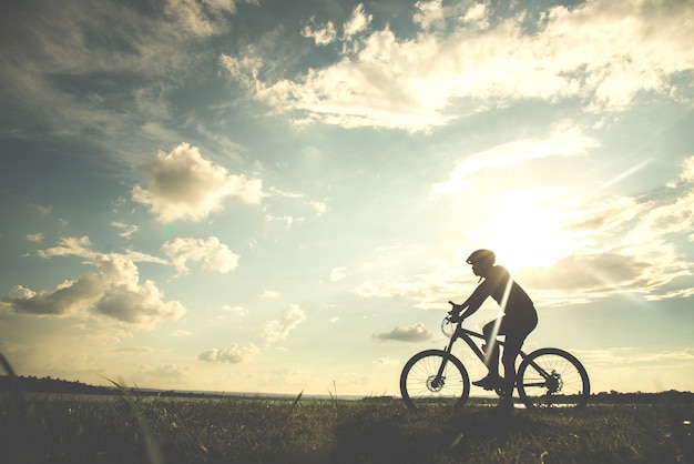 Silhouette young man of cycling on sunset background Premium Photo
