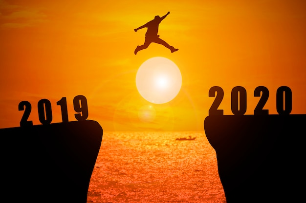 Silhouette of young man jumping from 2019 year to 2020 year with sun rise background Premium Photo