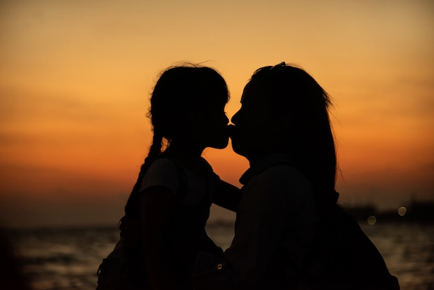 Silhouette of a young mother lovingly kissing her little daughter Free Photo