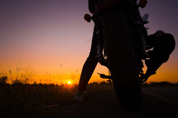 Silhouette of young woman drive with motorbike on street, enjoying freedom and active life Premium Photo