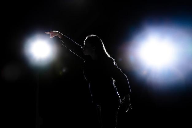Siluetta di giovane donna che gesturing isolato sulla parete nera con torce elettriche. copyspace. Foto Gratuite