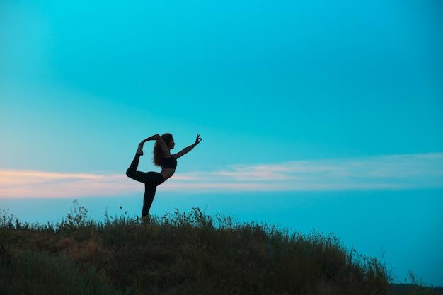 La silhouette della giovane donna sta praticando lo yoga Foto Gratuite