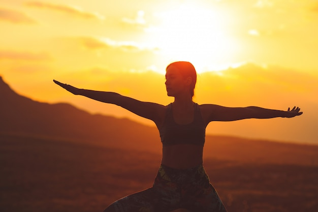 Silhouette of young woman practicing yoga or pilates at sunset or sunrise in beautiful mountain location. Premium Photo