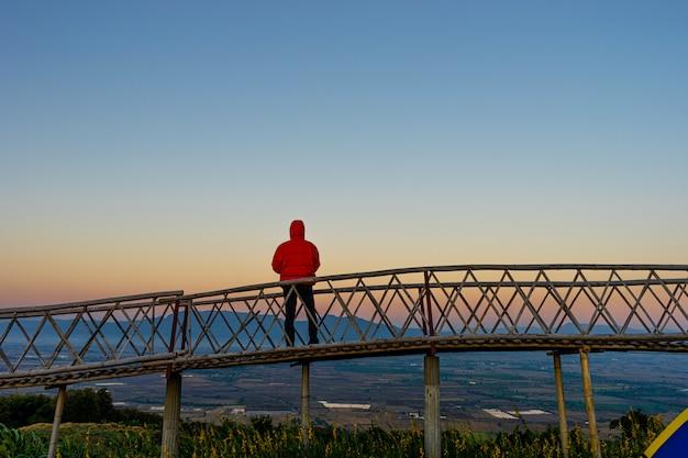 Silhouetted азиатского человека стоя на бамбуковом мосте на запрете doi sa-ngo chiangsaen, провинции chiang rai, таиланде. Premium Фотографии
