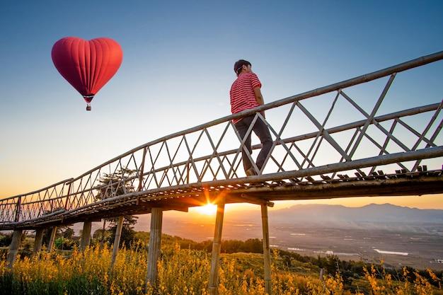 Silhouetted азиатского человека стоя на бамбуковом мосте с краснокалильным воздушным шаром в форме сердца над заходом солнца. Premium Фотографии