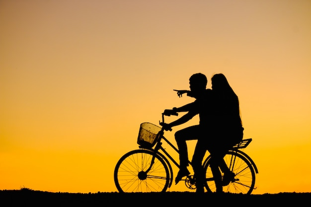 Silhouettes couples and bicycle on sunset sky Premium Photo