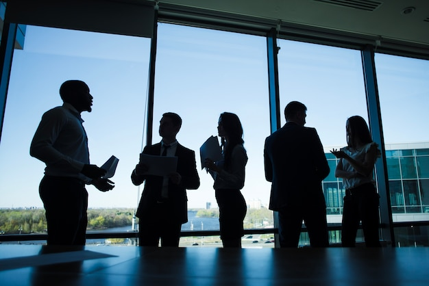Silhouettes of discussing business people Free Photo