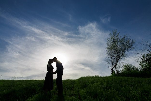 Silhouettes of love couples on the nature in summer evening.young man and woman tenderly embracing in the sunset. Premium Photo