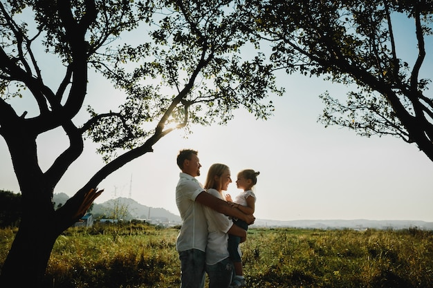 Silhouettes of lovely parents playing with their daughter under old trees Free Photo